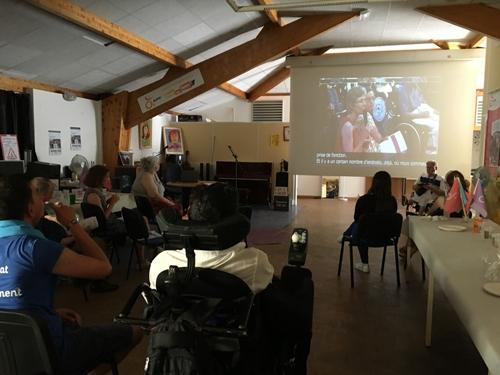 Des adhérents suivent l'AG de Lille en direct retransmise sur grand écran à la délégation de Paris