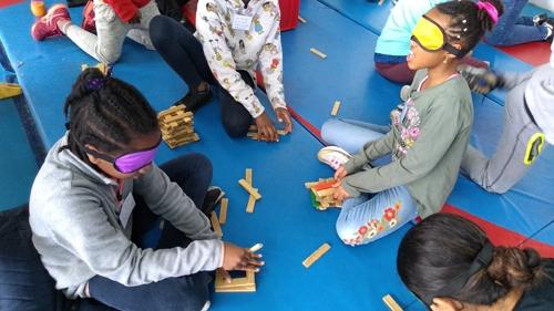 Photographie d'enfants avec les yeux bandés s'exerçant à un jeu de construction
