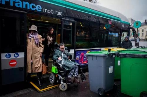 Alexandre essaye de descendre d'un bus face à un tas de poubelles sur le troitoir