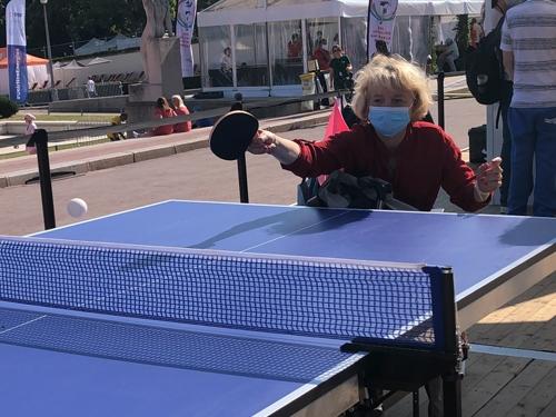 Hélène joue au ping pong sur un stand