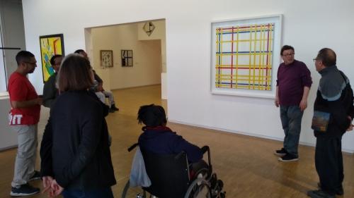Groupe de travailleurs de l'ESAT de Noisy-le-Sec écoutant le conférencier du centre Pompidou devant une peinture de Piet Mondrian