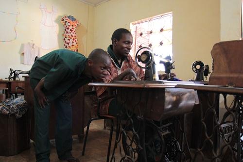 Deux élèves de couture penchés sur une machine à coudre