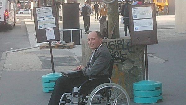 Photo de François Le Berre, en fauteuil, à un arrêt de bus