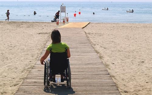 photo de personne en fauteuil de dos sur une plage