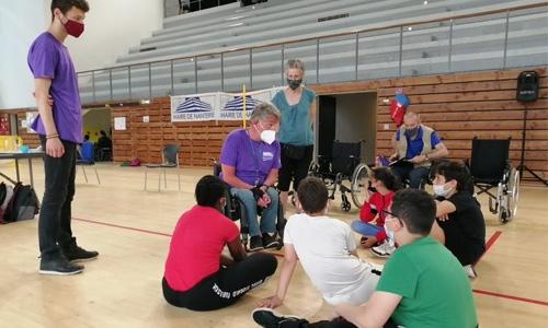 Franck, Aurélien, Claudie et Guy-Michel expliquant le handicap aux enfants avant de les faire monter sur un fauteuil roulant